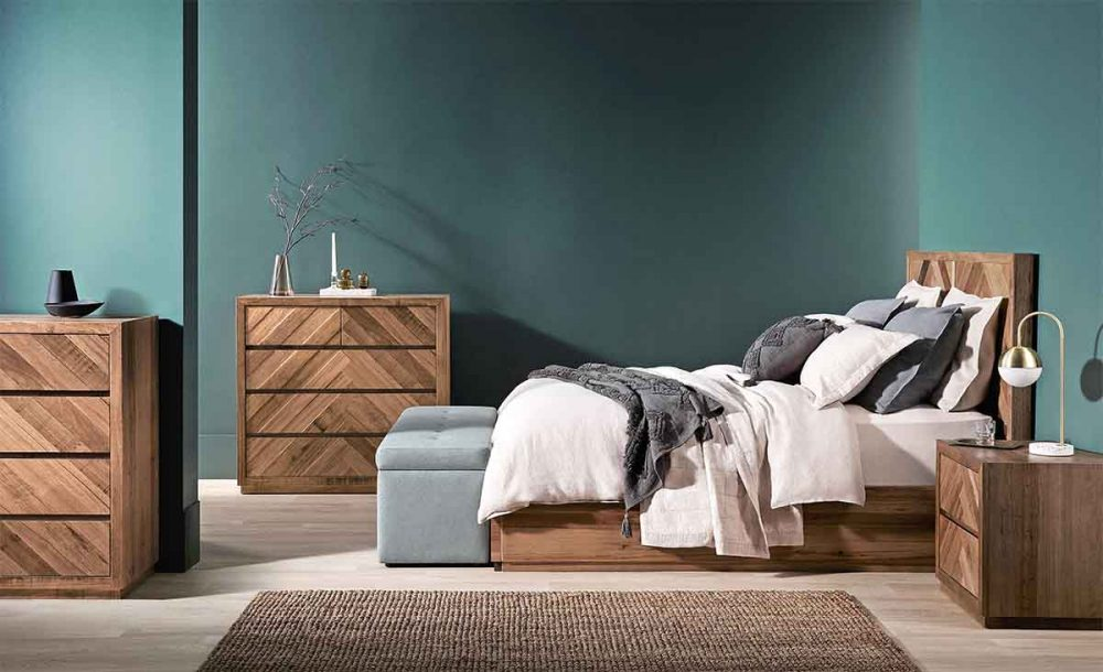 Natural timber bedroom furniture set against a slate green bedroom wall.