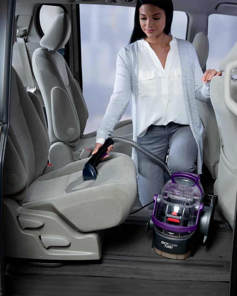 A person cleaning car seats with the Bissell SpotClean Turbo.