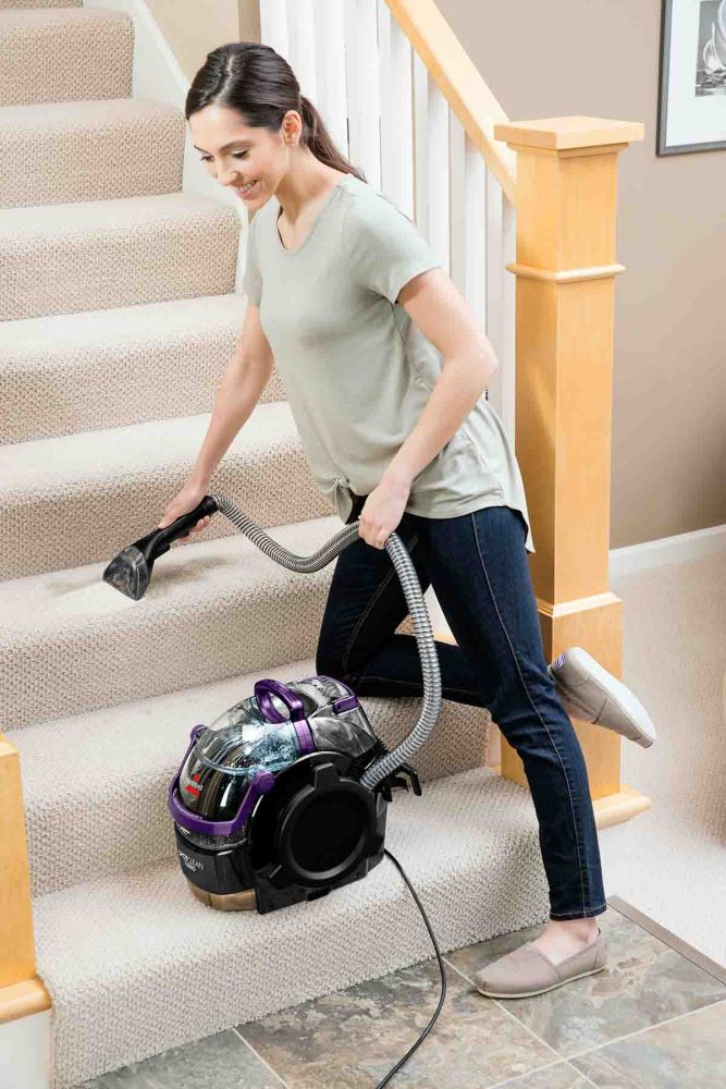 A person cleaning a staircase with the Bissell SpotClean Turbo.