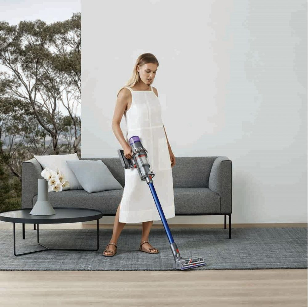 A woman using the Dyson V11 Absolute Extra to clean the lounge room carpet.