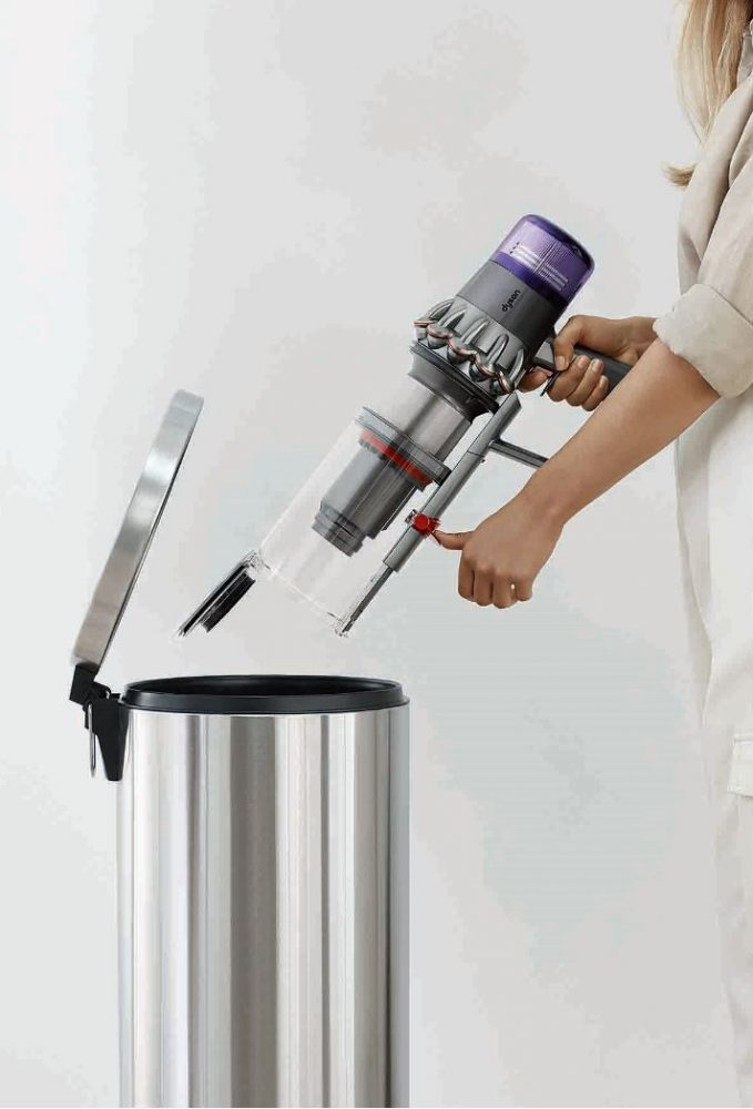 A person emptying the Dyson V11 Outsize Cordless Vacuum's large dustbin into the rubbish.