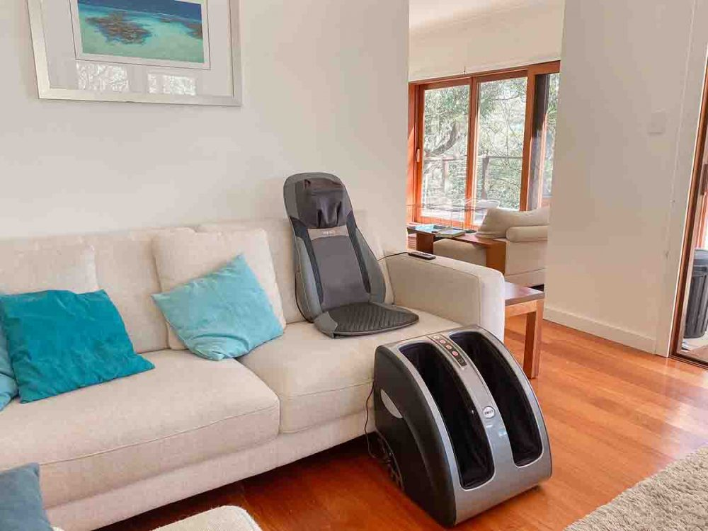 The HoMedics Shiatsu Elite II Massage Cushion and the HoMedics Supreme Foot and Calf Massager set up in a lounge room.
