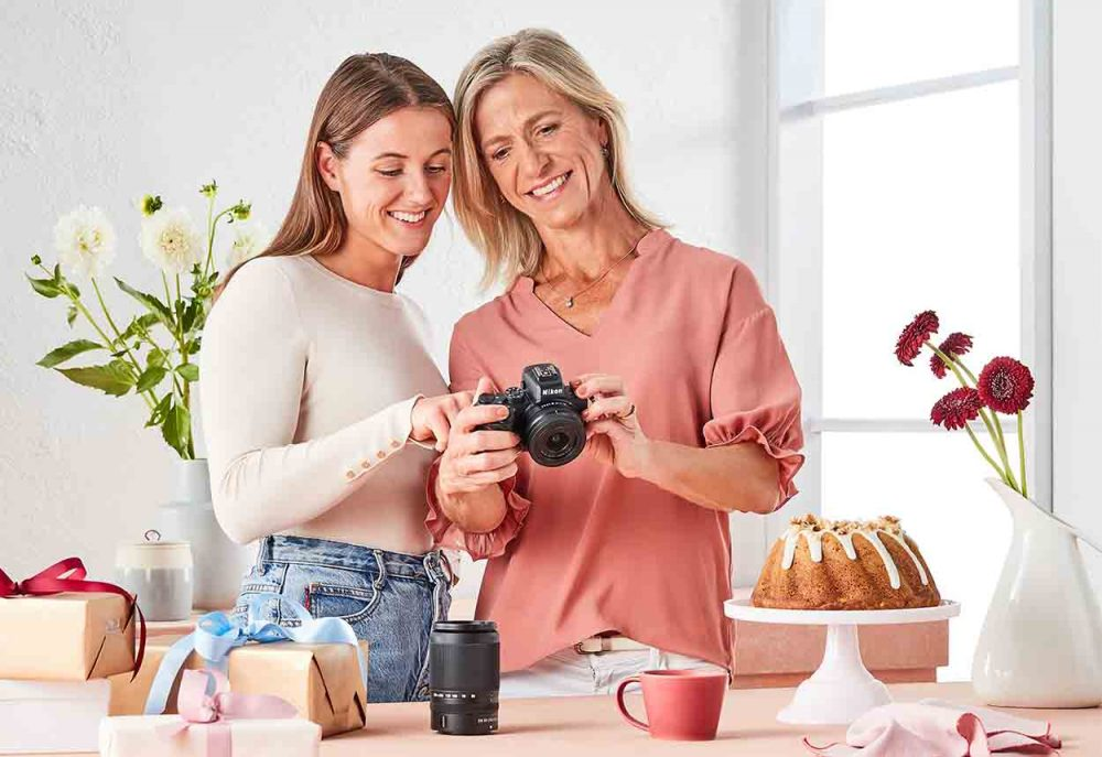 AFLW Player Nicola Barr and her Mum looking at a Nikon camera.