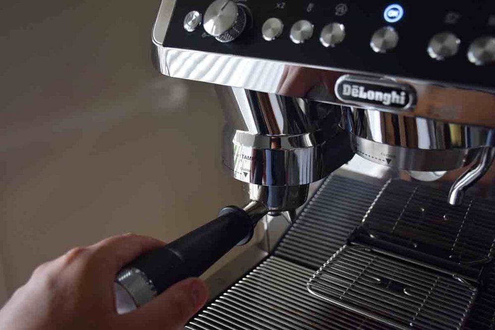 A person showing how to operate the De'Longhi La Specialista Maestro Coffee Machine.