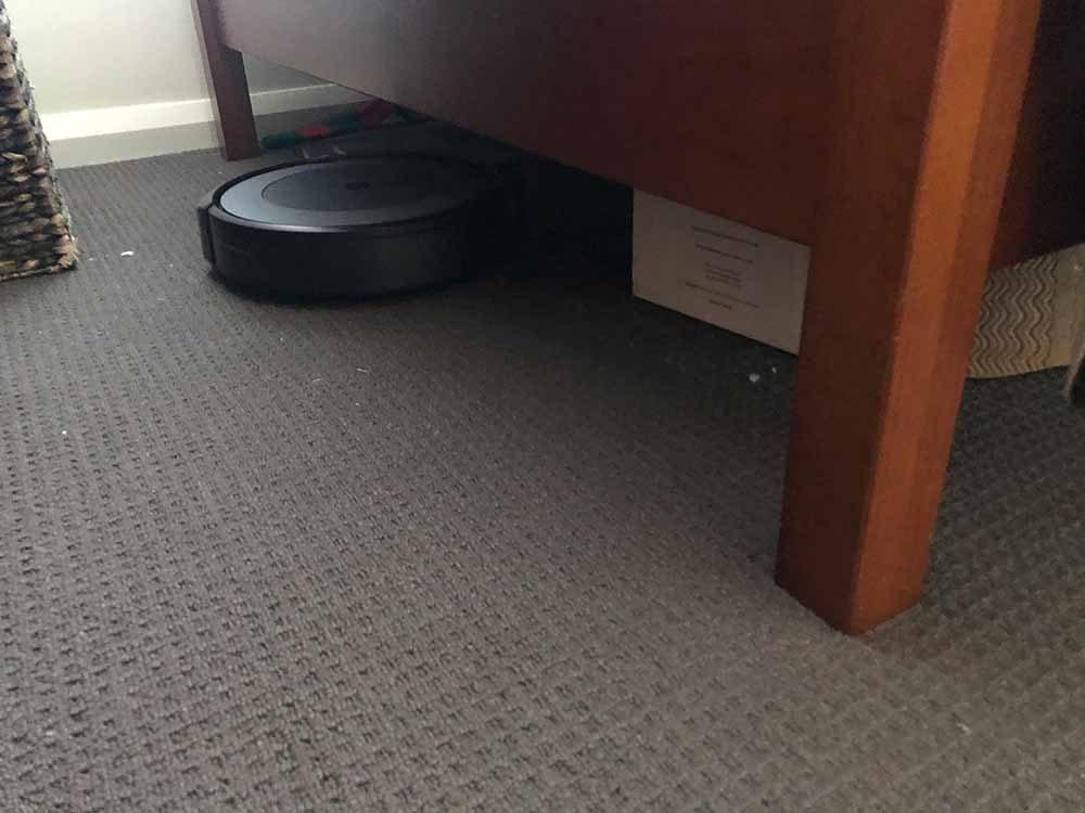 The iRobot Roomba i3+ vacuuming under a bed.