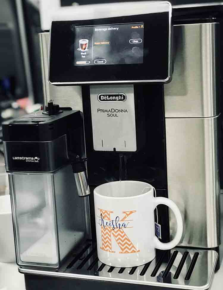 The De'Longhi PrimaDonna Soul Automatic Coffee Machine with a cup and tea bag in front of it.