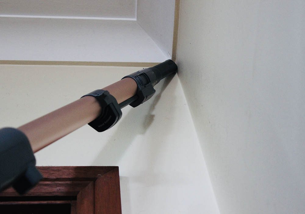 Vacuuming a high-to-reach corner of a ceiling with the Shark PZ1000 Vacuum.