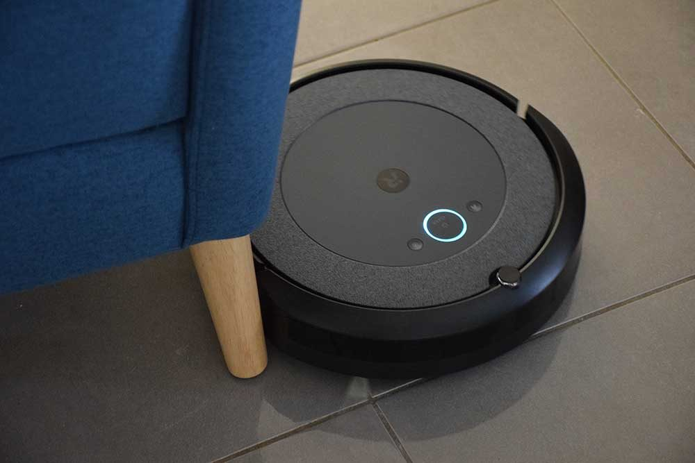 The iRobot Roomba i3+ cleaning next to chair.